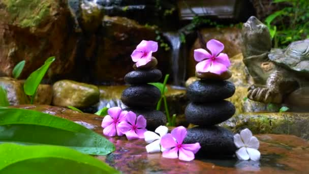 Stones stacked into pyramid with pink flowers on top. Zen, beauty or wellness concept.