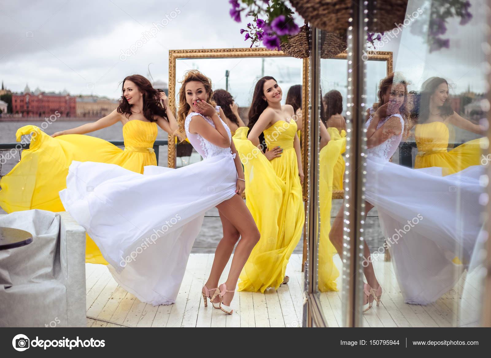 Noiva linda e duas damas de honra em vestidos similares amarelos juntos em  um verão terraço aead4d096f07