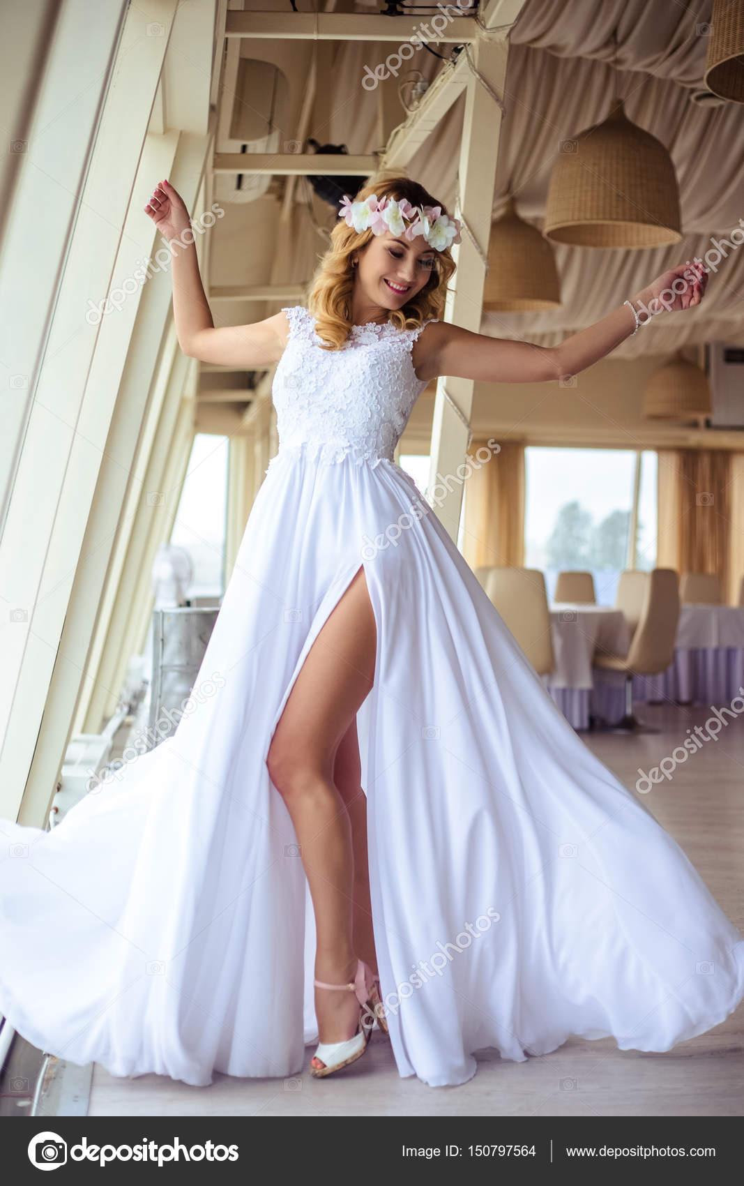 Sexy novia rubia joven en un vestido de novia blanco de crucero en ...