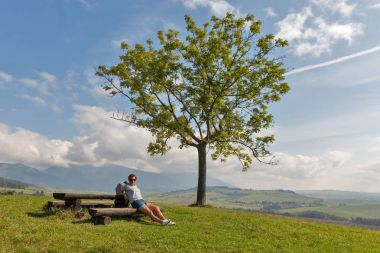 Woman sitting on summer hill near Liptovsky Trnovec, Slovakia.