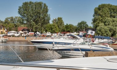 KYIV, UKRAINE - JUNE 05, 2015: People visit modern yachts moored on Dnieper river during IBYS, International Boat and Yacht Show with the latest technologies for sailing in Chervona Kalyna yacht-club.