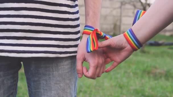 Hände mit Regenbogen-LGBT-Bändern am Handgelenk. Schwules Paar hält sanft Händchen und streichelt sich gegenseitig
