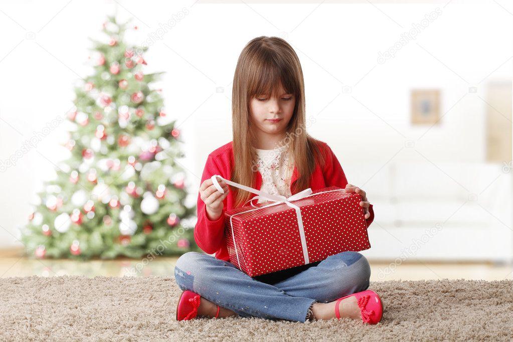 Mädchen öffnen ihr Weihnachtsgeschenk — Stockfoto © Sepy #127839310