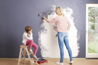 woman  and daughter painting wall