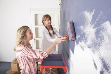 daughter painting wall while her mother