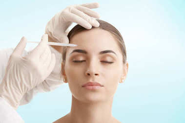 Portrait of an attractive young woman receiving botox treatment. Isolated on light blue background.