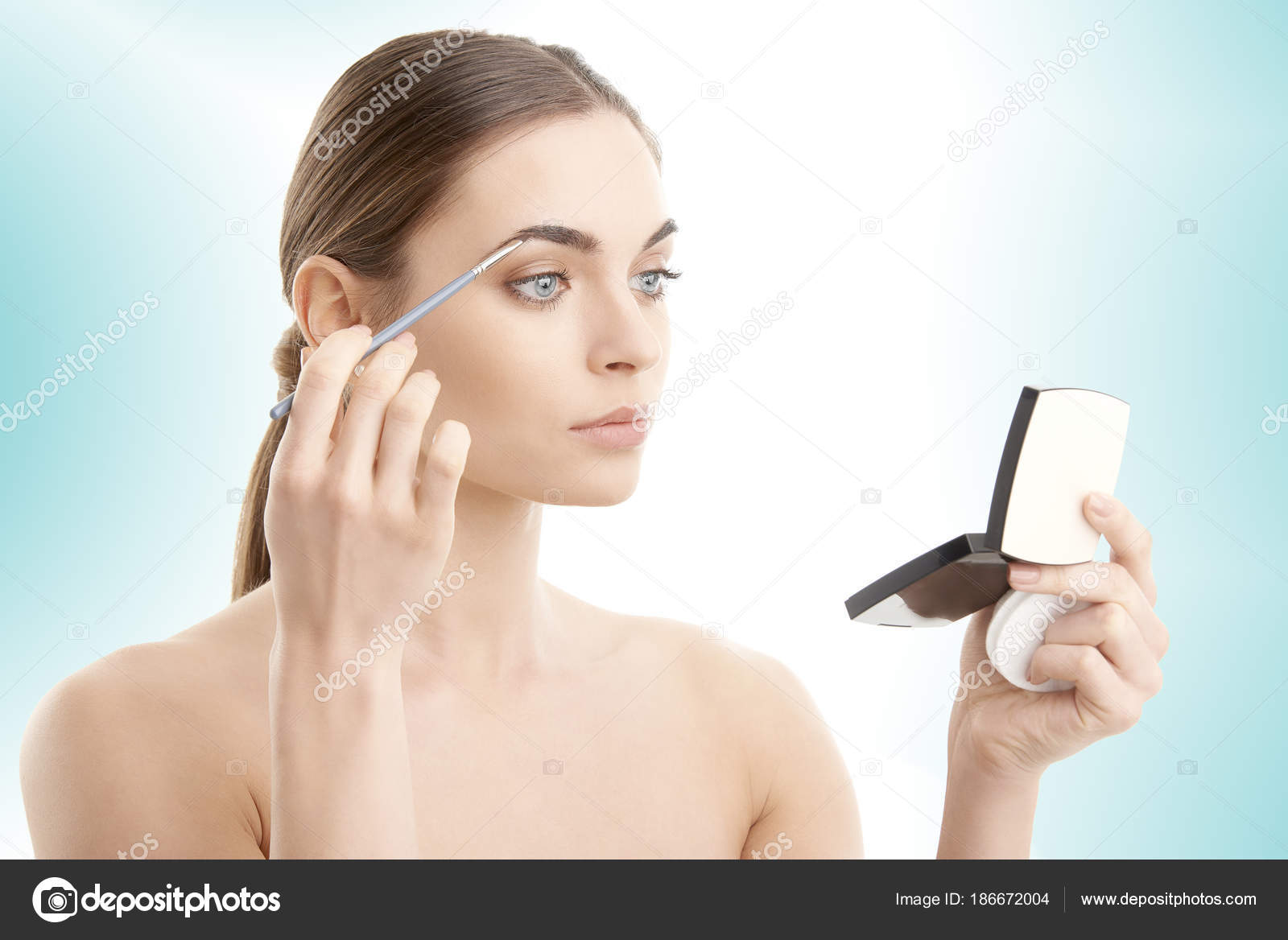 woman holding hand mirror. Studio Shot Of A Beautiful Young Woman Applying Makeup To Her Eyebrow And Holding Hand Mirror In While Standing At Isolated Light Blue Background. G