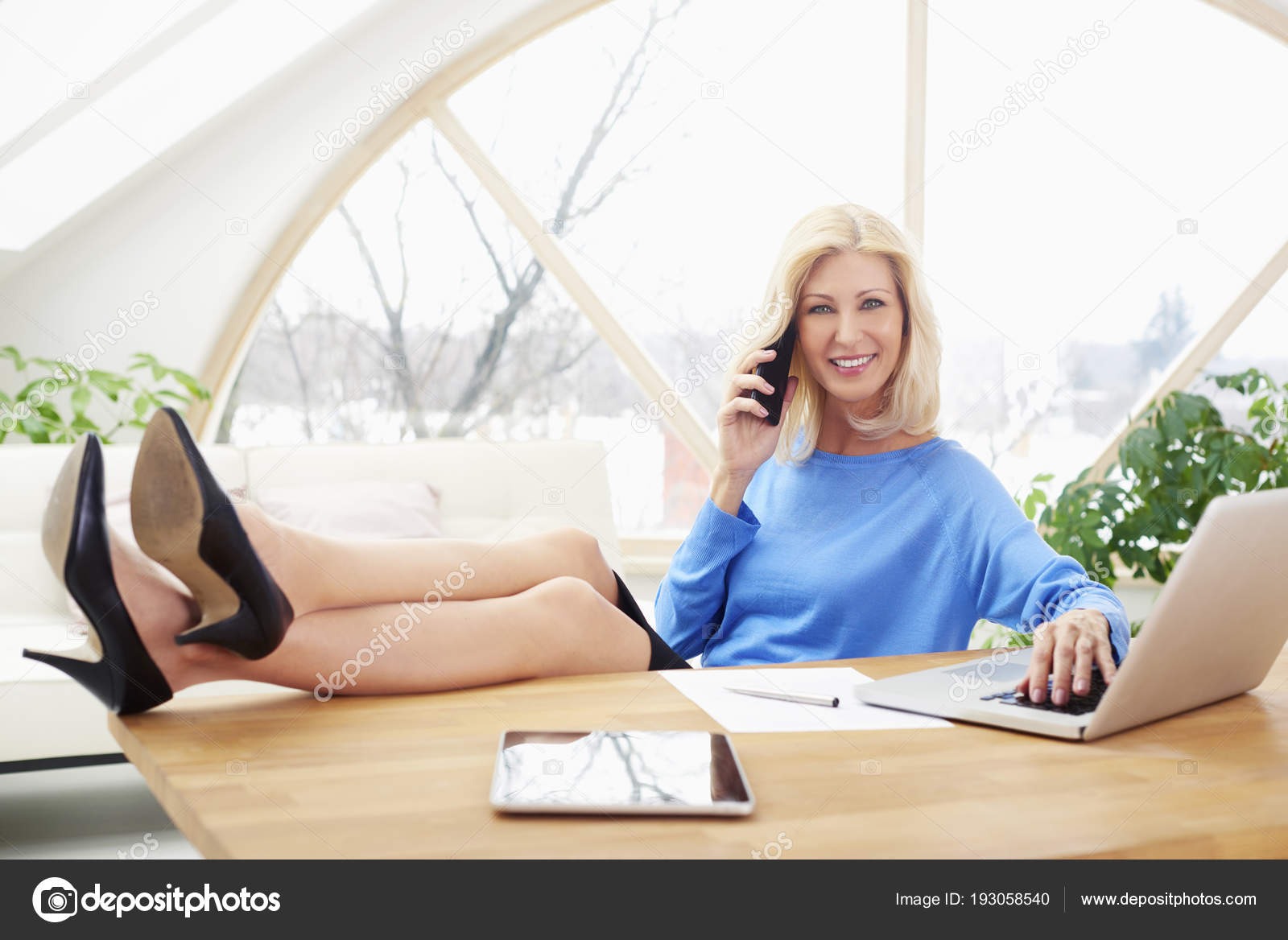 sales working home office. Full Length Shot Of A Middle Aged Blond Sales Woman Sitting With Legs On Office Desk And Talking Somebody Mobile Phone While Working Laptop. Home