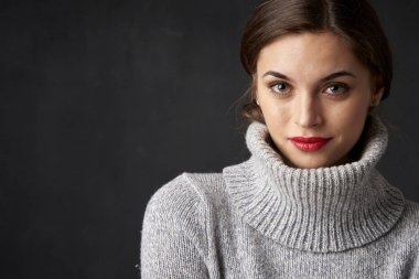 Portrait of beautiful woman wearing turtleneck sweater while standing with arms crossed at dark background.