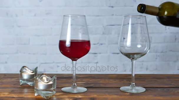 Frau gießt bei romantischer Party mit Freundin Rotwein ins Glas
