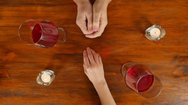 Láska pár, pití vína a drželi se za ruce. Romantická večeře.