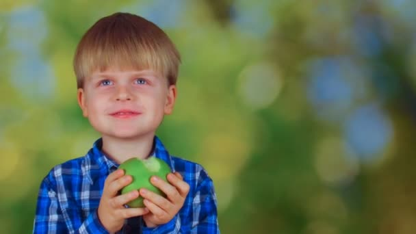 Cute little boy eating green apple and smiling