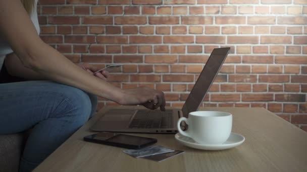 Online vásárlás koncepció. Nő kezében gazdaság hitelkártya és használ laptop, lassított hd videó