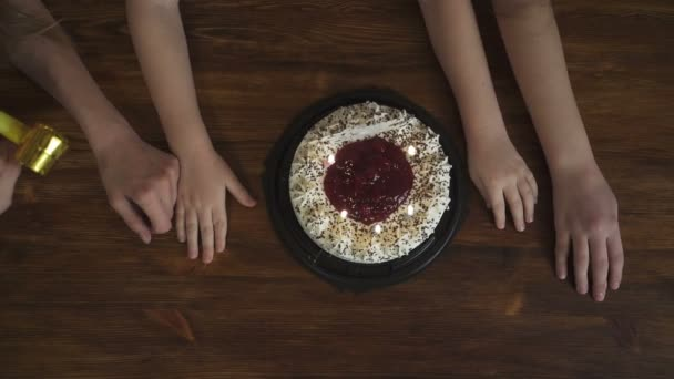 Boy blows out the candles on cake, top view slow motion video. Birthday party concept.