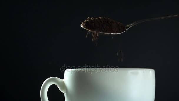 Instant coffee pouring from spoon to white mug, close-up slow motion hd video