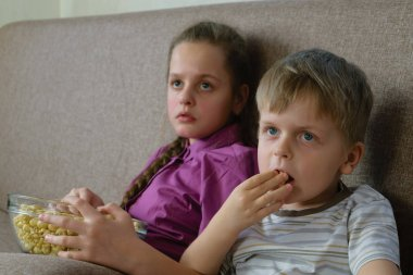 Boy and girl watching TV and eating popcorn