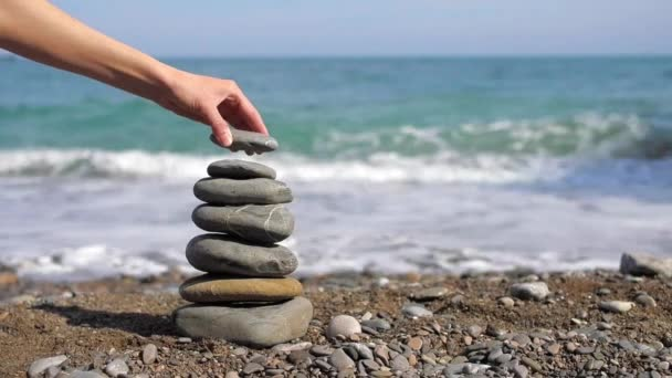Womans hand puts pebble in pyramid on the sea