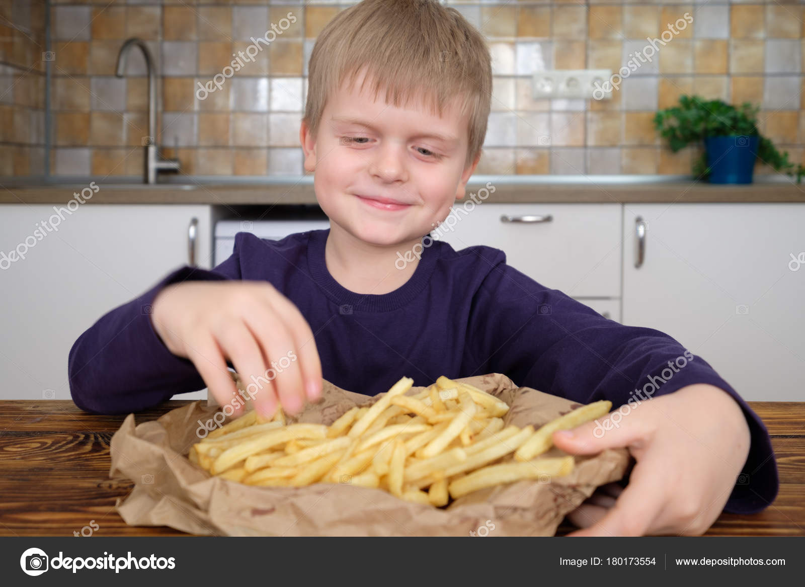 2ad223a855d8a Cute little boy enjoying french fries on kitchen — Stock Photo ...