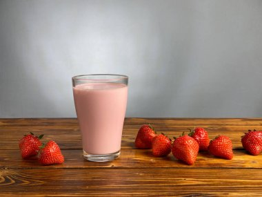 Strawberry yogurt or smoothie in glass on wooden table