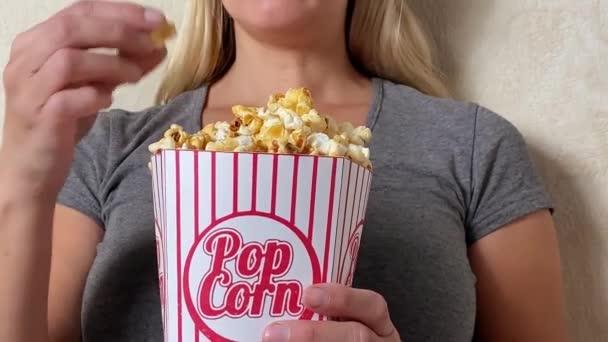 Lány tévézik és popcornt eszik otthon a kanapén.