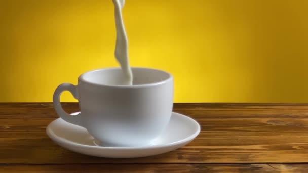 Krémové mléko nalévající se do šálku s kávou.