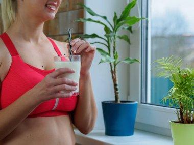 Sporty girl drinking a milkshake near the window, slow mo