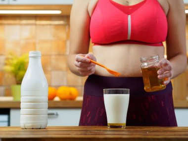 Sporty girl puts honey in a glass of almond milk, slow motion