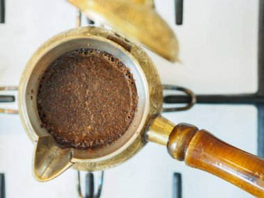 Traditional turkish coffee pot on gas cooker with hot coffee