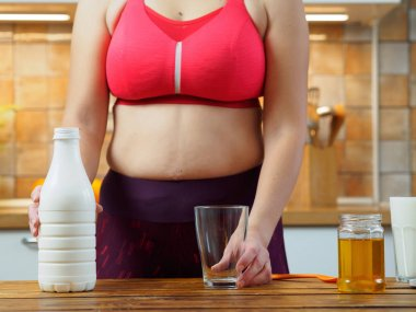Sporty girl puts honey in a glass of almond milk