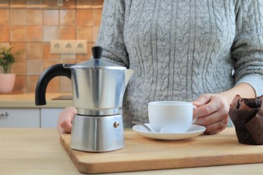Woman preparing coffee for breakfast and pouring it in cup