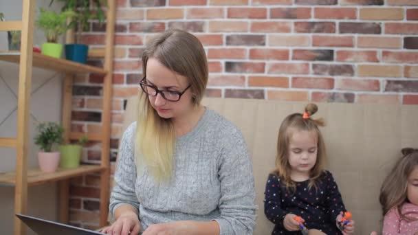 Zwei kleine Mädchen spielen in der Nähe der Mutter und lassen sie zu Hause nicht arbeiten