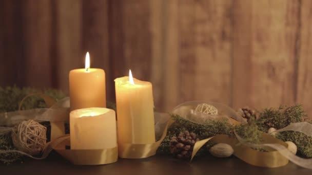 Weihnachtsstimmung mit beweglichen Flammen aus drei brennenden Kerzen, Tannenzweigen, natürlichen Tannenzapfen, goldenem Satin und weißen Organza-Bändern