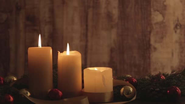 Christmas setting with lighted candles with moving flames, pine boughs, natural pine cones, red and gold baubles, satin ribbon decorations filmed in bokeh effect transition