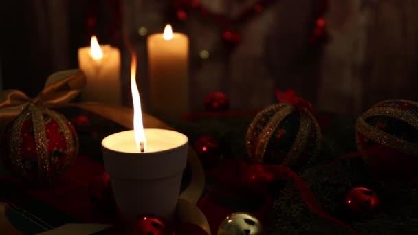 Vánoční nálada: tři zapálené svíčky, jedna s velkým plamenem v popředí, červené a zlaté ozdoby, oddělovací kuličky, saténová zlatá stuha, vánoční ozdoba na dřevěném pozadí natáčené v bokeh efektu