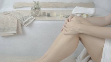 Woman holds her bare legs in white towel sitting in her modern spa design bathroom