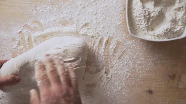 Lassan mozgó felső nézet az ember kezét masszírozó pizza tészta, hogy előkészítse a kovászos otthon egy könnyű fa tábla fehér liszt