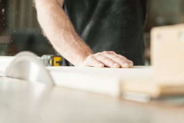 hand of a carpenter using a miter saw