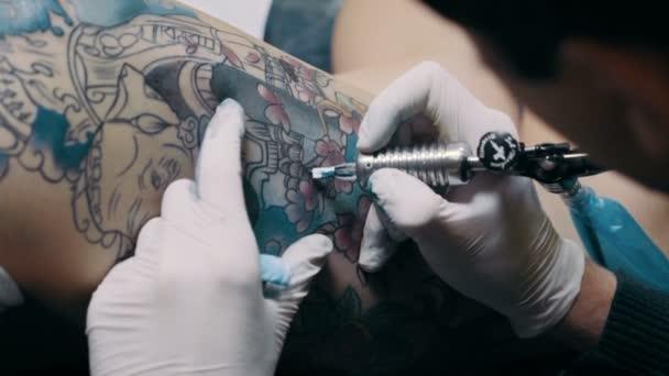 umělec ukazuje proces získání tetování