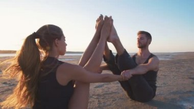 couple doing yoga during sunset