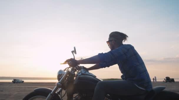 Muž na koni motocyklu na pobřeží