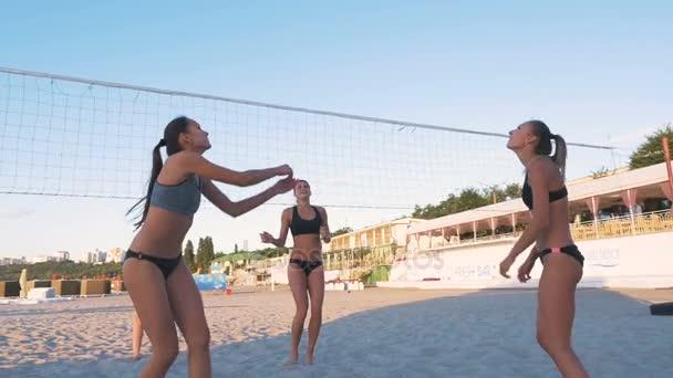 ženy hrají volejbal při západu slunce