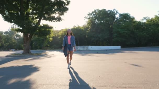 bokovky žena s longboard v parku