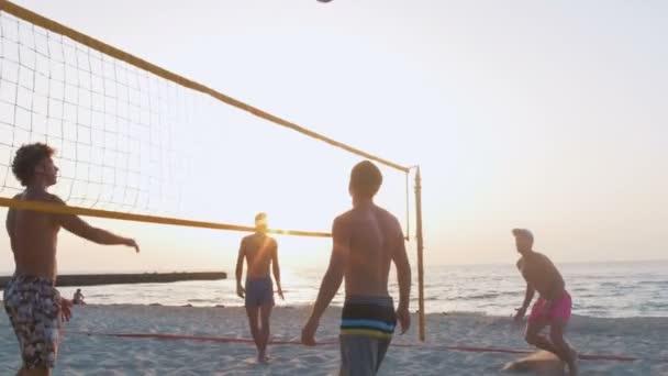 muži hrají volejbal při západu slunce
