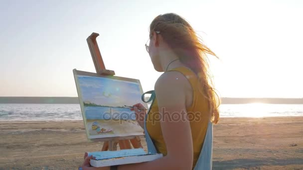 female artist painting on beach