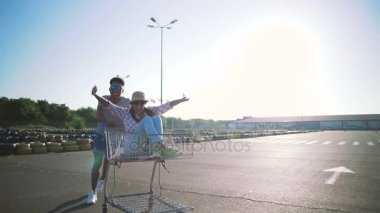 Couple have fun with shopping cart