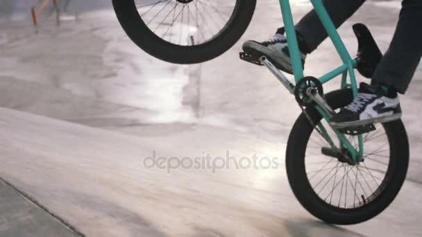 Nahaufnahme des männlichen Beine auf grün bmx-Bike machen Tricks im Skatepark, Slow-Motion