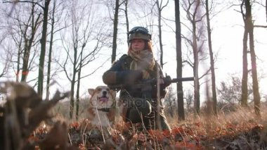 woman in protect uniform with gun at autumn forest play with dog