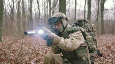 male in protect uniform with gun at autumn forest play strikeball