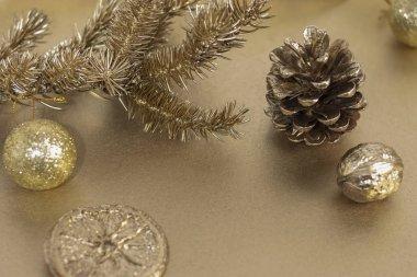 Christmas or New Year composition. Christmas tree branch with a toy, pine cone and orange slice in gold color. Holiday and celebration concept for greeting card or invitation. Copy space