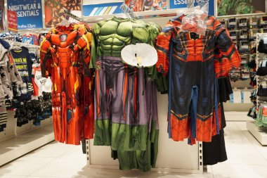 Spiderman, Superman, Ironman etc action figures costume for kids hanging for sale inside a boutique shop in a mall. : Children costume dresses hanging for sale. Dubai UAE - May 2020
